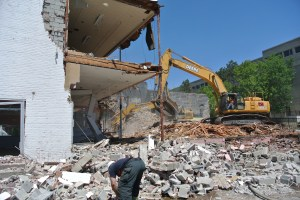 An excavator topples walls and gathers rubble toward the end of demolition of the Ruderman's Building.