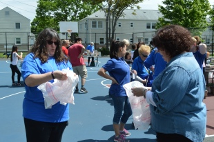Kiwanis members double up bags for families to tote home books.