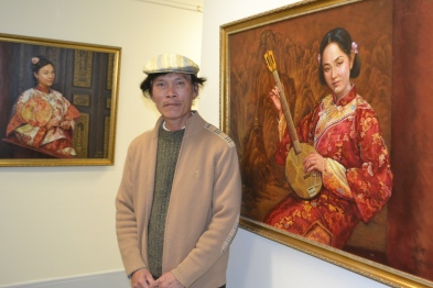 Ming Huang Zhang is a Malden resident, Chinese immigrant and accomplished painter, shown here exhibiting his work at the MATV Gallery in Malden.