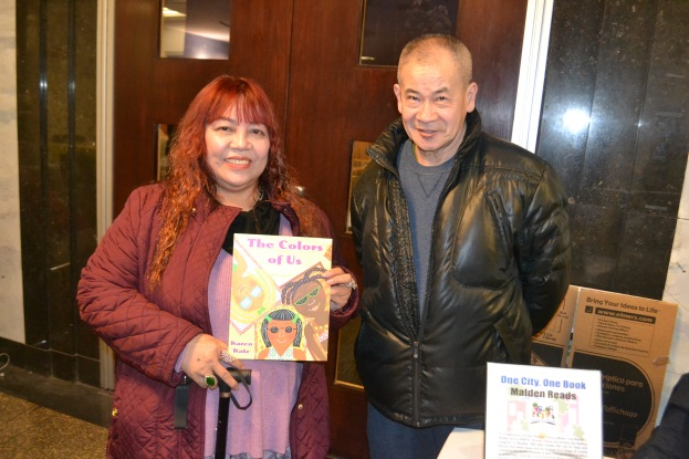 Anna Thai and Truong Le holding up one of the Malden Reads companion books.