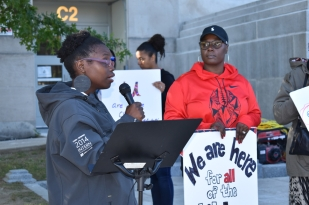 Bridget Mutebi, a Boston-based educator and member of MaldenCORE speaks (left). Erga Pierrette rally emcee, on right.