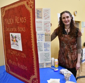 """Artist Karen Alzayer with her participatory art project, """"Malden Reads: Influential Books."""" Photo by Diana Jeong"""